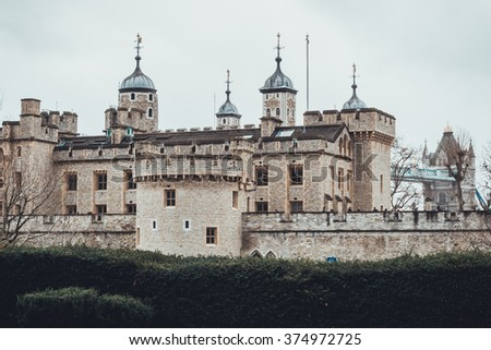 Exterior view of the stone facade of the Tower of London, a famous landmark and tourist attraction, on a grey cloudy day - stock photo