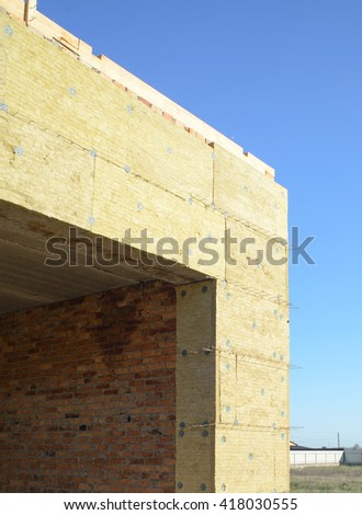 Exterior wall heat isolation with mineral wool in private house, building under construction - stock photo