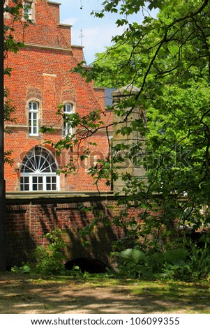 External facade of an old red brick manor with arched windows in a tranquil leafy setting amongst trees