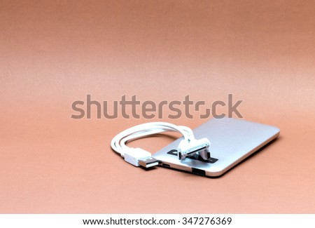External hard disk isolated on brown background. - stock photo