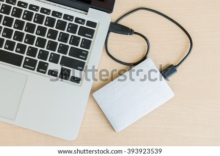 External hard drive connected to laptop computer - stock photo