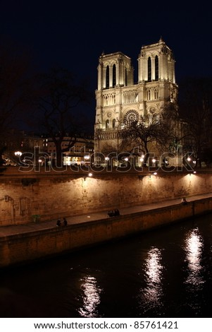External night view of the Cathedral of Notre Dame from a bridge over the River Seine