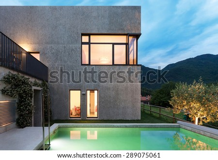 external of a modern house with pool, night scene - stock photo