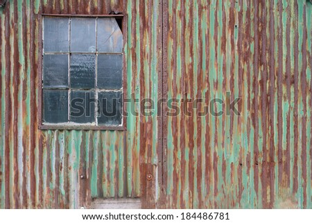 External rusty corrugated iron wall with weathered green paint of a dilapidated old building with a cottage pane window with a broken pane of glass in an architectural background - stock photo