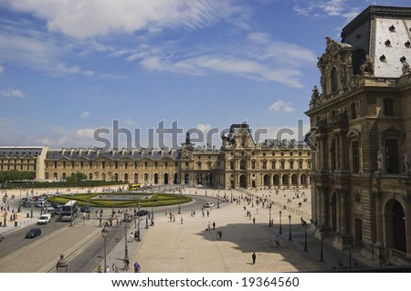 External view of section of Louvre Museum looking at the inverted glass pyramid traffic circle under summer blue sky