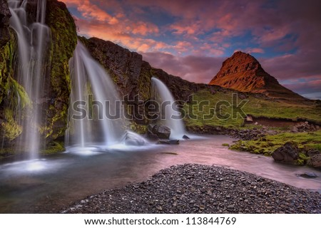 Extinct volcano in Iceland (Island). Sunset at Mount Kirkjufell (Church mountain) in the Snaefellsnes peninsula, Iceland, complimented by a beautiful waterfall. - stock photo