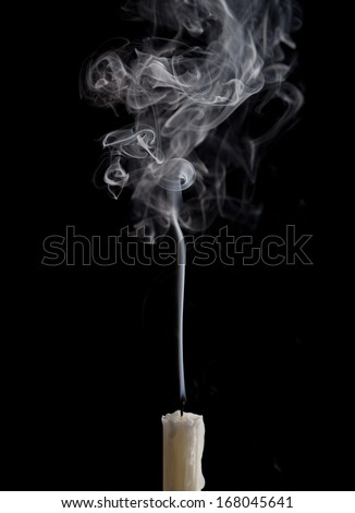 extinguished candle with smoke, isolated over black - stock photo