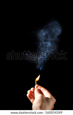 Extinguished match in the human hand on a black background.
