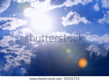 Extra-bright sun and cloudscape with vibrant color - intentional flare and chroma for added drama. - stock photo