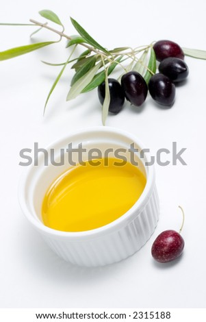 Extra-virgin olive oil and black olives branch on white paper