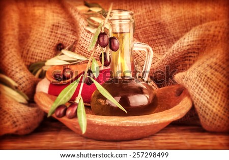 Extra virgin olive oil in the bottle decorated with fresh ripe olive branch on burlap background, beautiful food still life, healthy eating concept - stock photo