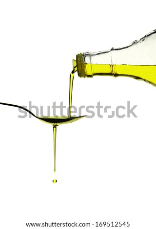 Extra virgin olive oil pouring over a spoon isolated on white with a clipping path - stock photo