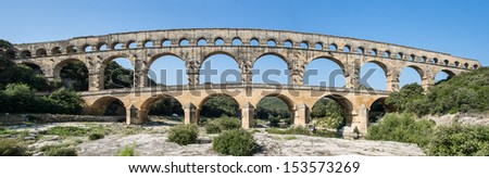 Extra wide angle shot of Pont du Gard in the morning, an old Roman aqueduct near Nimes in Southern France - stock photo