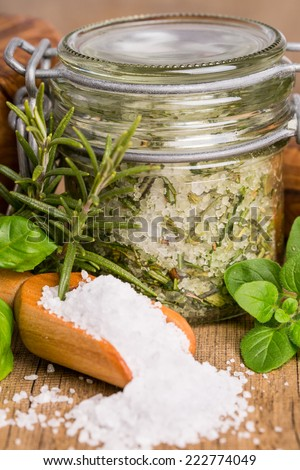 Extract of herb salt with ingredients on wooden board - stock photo