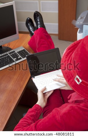 Extraordinaire young businesswoman in red with legs over desk - stock photo