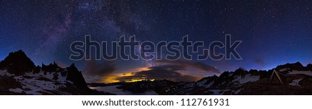 Extraordinary 360 degree panorama of the night sky in the Swiss alps at 2700+ meters. Visible is a glow from a city and the majestic milky way above it - stock photo