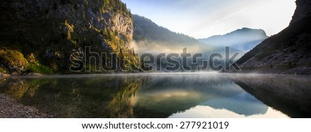 Extraordinary, fairy tale, mythological mountain lake scenery in a glacial valley, with sun shining to the rocky slope and morning mist above the lake surface with perfect reflection.  - stock photo