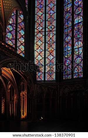 Extraordinary stained glass windows define the interior of St. Chappelle Cathedral in Paris, France - stock photo