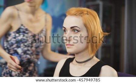 Extravagant girl in a black dress and with the red color of hair in a beauty salon. For her Master makes meykap. - stock photo