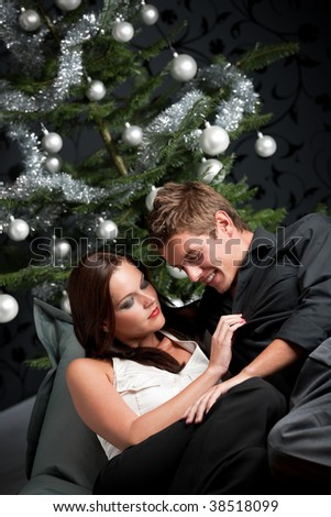 Extravagant man and woman in front of Christmas tree and black wallpaper - stock photo