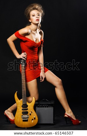 Extravagant model in a red dress with electric guitar and amplifier - stock photo
