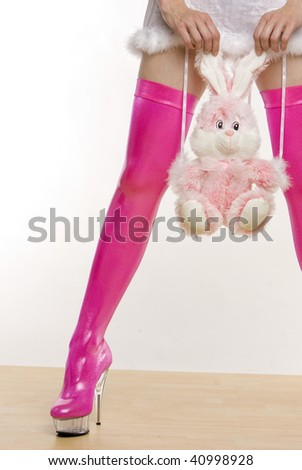 extravagant pink boots and hands holding a rabbit toy