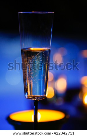 Extravagant, private romantic candlelit champagne glass with a jacuzzi in the background. Love, celebration, relax, romance, luxurious vacation, wellness spa concept.  - stock photo