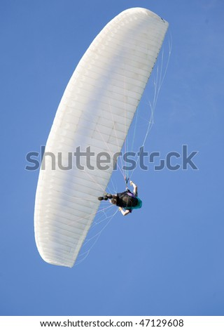 extreme active paraglider flying over a blue sky - stock photo