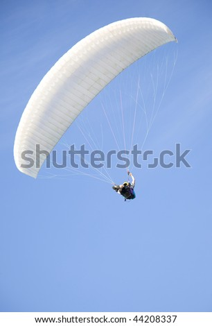 extreme active paraglider flyng over a blue sky - stock photo