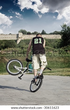 Extreme bicycle rider performing freestyle tricks on his bike. - stock photo