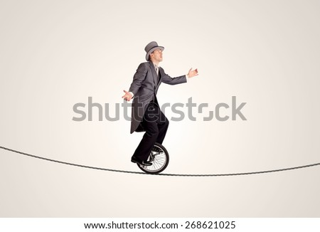 Extreme business man riding unicycle on a rope concept on background - stock photo