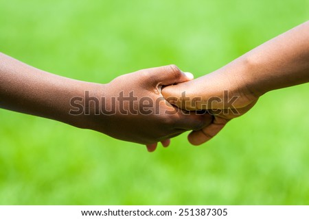 Extreme close up detail of African kids holding hands against green outdoor background. - stock photo