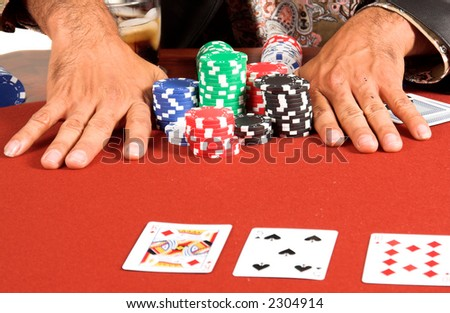 Extreme Close up detail of the hands of a male Texas Hold um poker player going all in on a red felt table - stock photo
