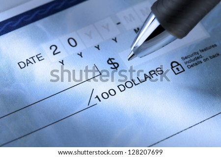 Extreme close-up image of a ballpoint pen and a cheque.