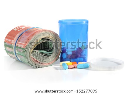 Extreme close-up image of tablets and container with roll of money - stock photo