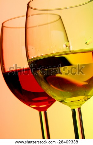 Extreme close-up image of two glasses of wine with red and green background