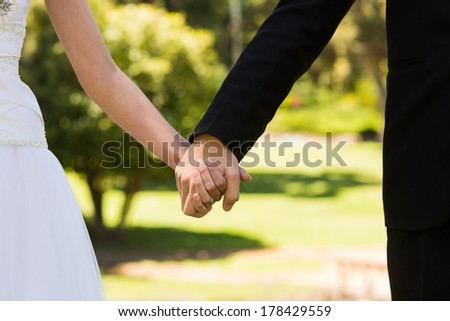Extreme close-up mid section of a newlywed couple holding hands in the park - stock photo