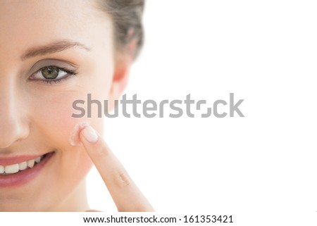 Extreme Close up of a beautiful young woman applying cream to her face over white background - stock photo
