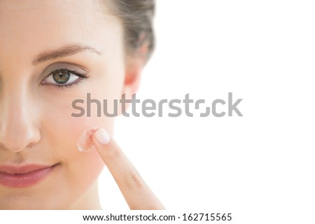 Extreme Close up of a beautiful young woman applying cream to her face over white background
