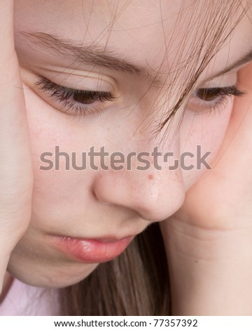 Extreme close-up of a girl's face looking serious - stock photo