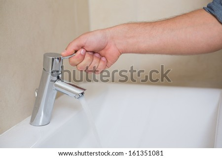 Extreme Close up of a plumber's hand opening a water tap at bathroom