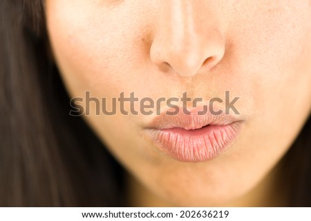 Extreme close-up of a young woman puckering - stock photo
