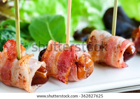 Extreme close up of appetizing dates with grilled bacon finger food. Mounted on small skewers. - stock photo