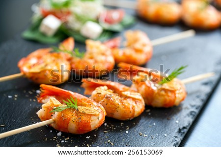 Extreme close up of appetizing grilled queen prawn tail brochettes. - stock photo