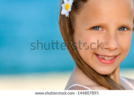 Extreme close up of cute girl smiling at seaside.