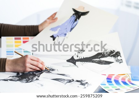 Extreme close up of fashion designer at work with fashion sketches and color charts. - stock photo