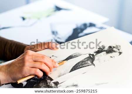 Extreme close up of female fashion designers hand creating fashion sketch. - stock photo