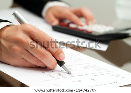 Extreme close up of female hand with pen pointing on cash flow document. - stock photo