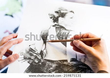 Extreme close up of female hands making fashion sketch. - stock photo