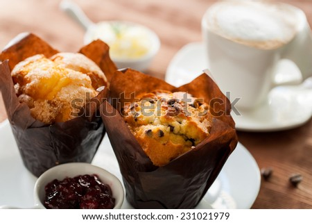Extreme close up of fresh muffins with creamy coffee in background. - stock photo